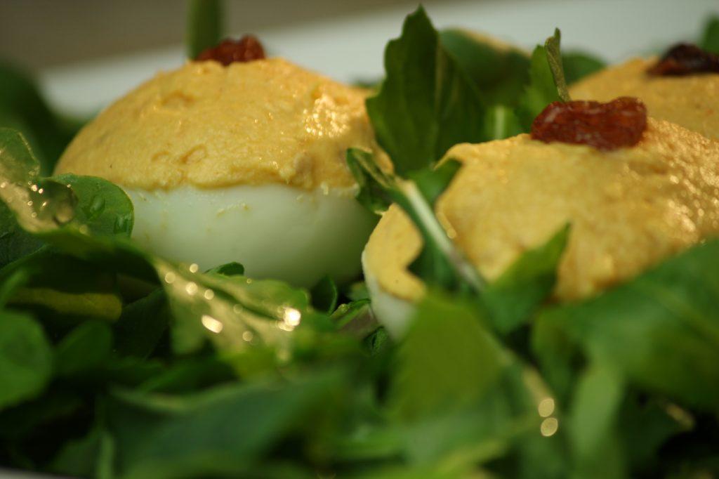 Ingredientes: 6 huevos 1 tomate grande Pasas 1 cebolla pequeña 2 ajos Zumo de ½ limón 2 cucharadas de coco rallado Aceite de oliva 2 cucharaditas de curry Sal Perejil Picar la cebolla, el ajo y el tomate muy finos. Calentar el aceite en una sartén y dorar las cebollas y el ajo. Añadir el curry y cocinar un par de minutos, añadir el tomate, el zumo de limón, el coco rallado, salar y cocinar removiendo hasta que quede una mezcla espesa. Dejar enfriar. Cortar los huevos en dos mitades iguales. Extraer las yemas, mezclarlas con la preparación del curry y batimos. Poner una pasa en cada huevo, rellenar los huevos y decorar con una pasa encima. Montar sobre una cuna de lechuga cortada en juliana.